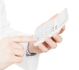Medical doctor with a calculator in his left hand calculating costs and revenues in physician practice and hospital fees
